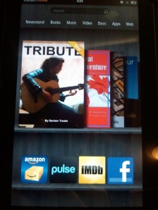 """Tribute"" looks nice on the Kindle bookshelf, and you can just see ""The Great Canadian Adventure"" behind it."